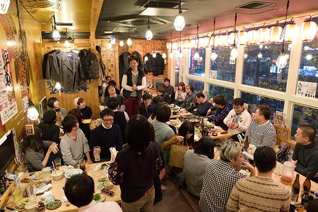写真:岡山WEBクリエイターズ年末スペシャル2017懇親会で締めの挨拶をしている後藤さんと見守る参加者