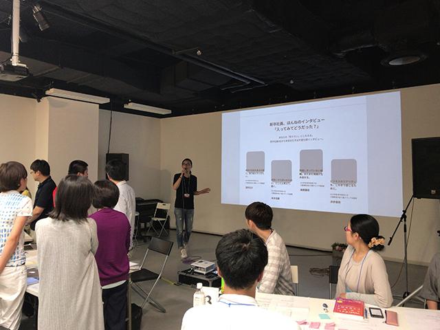 写真:ワークショップ後の意見交換を呼びかけている松田さんと意見交換をする参加者